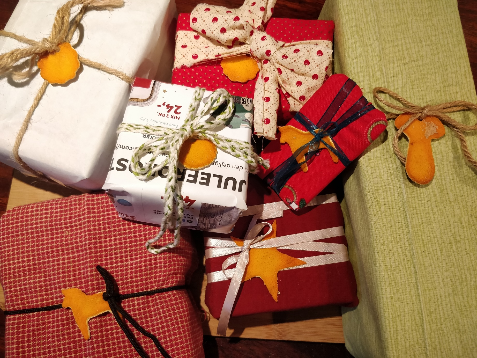 Bæredygtigt indpakkede julegaver i stof og genbrugspapir og med gavemærker af appelsinskræl