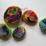 Filtbold i mange forskellige farver der er klippet op og lavet til en uro